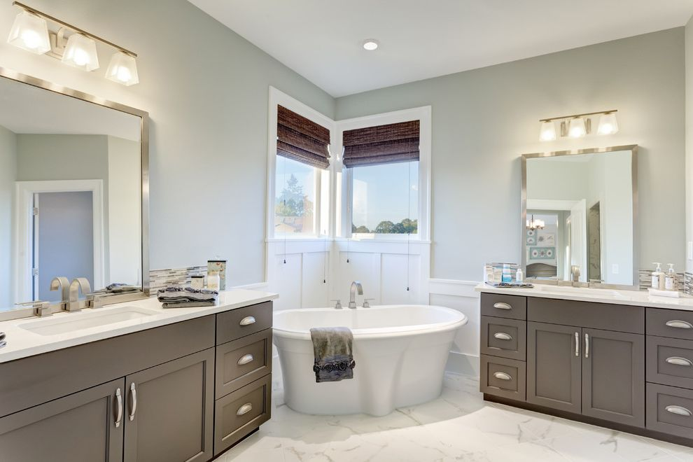 55 Inch Freestanding Tub with Traditional Bathroom Also Corner Corner Window Cup Pulls Double Sinks Double Vanity Framed Mirrors Freestanding Tub Light Gray Wall Marble Floor Neutral Colors Roman Shades Sconce Shaker Panel Cabinets Soaking Tub