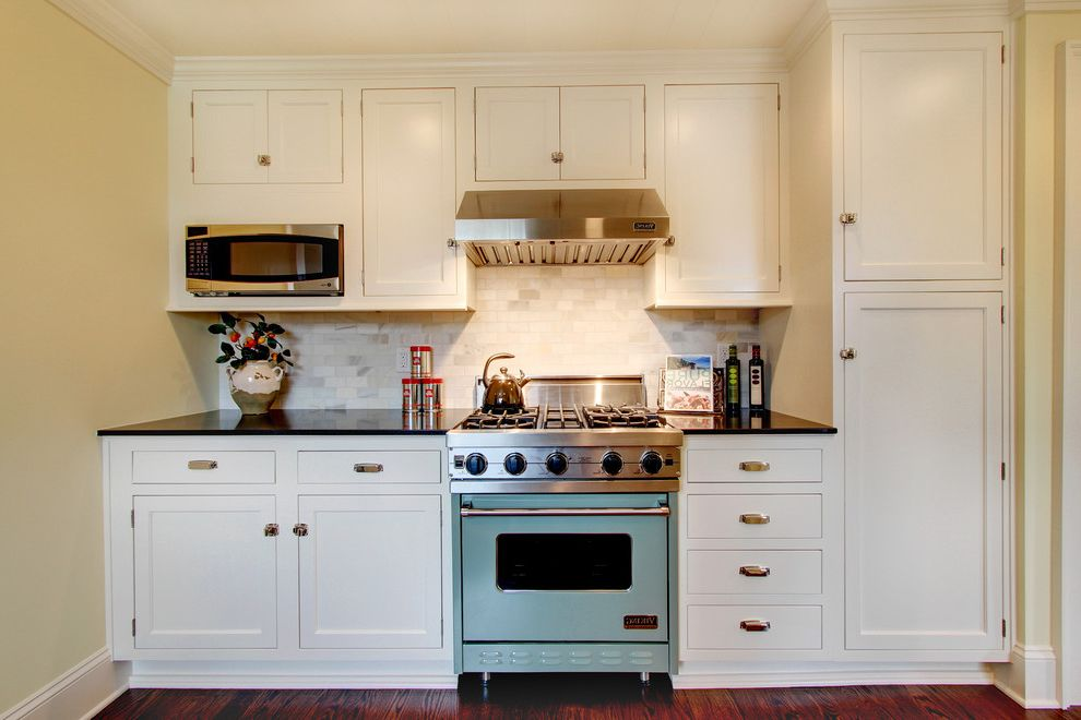 Above Range Microwave   Farmhouse Kitchen  and Crown Molding Drawer Pulls Hood Tile Backsplash Viking Range White Cabinets Wood Floor Yellow