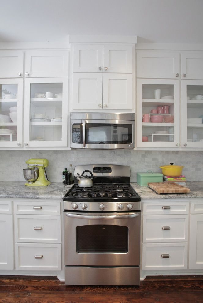 Above Range Microwave with Eclectic Kitchen  and Backsplash Glass Cabinet Doors Marble Tile Microwave Shaker Cabinets Stainless Stove White Kitchen Wood Floor Yellow Mixer