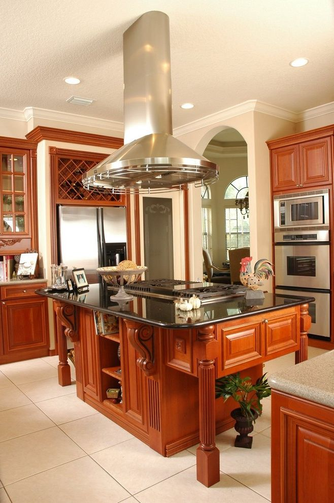 Above Range Microwave with Traditional Kitchen  and Arch Kitchen Kitchen Island Range Hood Recessed Lighting Stainless Steel Appliances Tile Floor Vent Hood Wine Rack Wood Cabinets Wood Trim