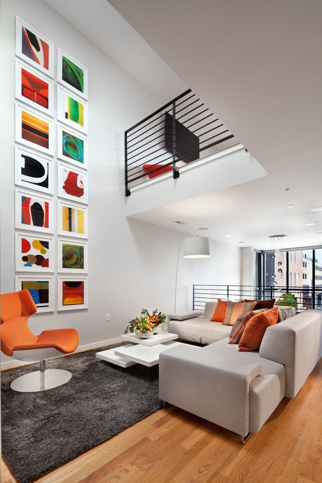 Alexandria of Carmel Apartments   Contemporary Family Room Also Black Railing Colorful Artwork Framed Artwork Gallery Wall Gray Area Rug Gray Sectional Sofa Orange Lounge Chair Recessed Lighting White Coffee Table White Floor Lamp
