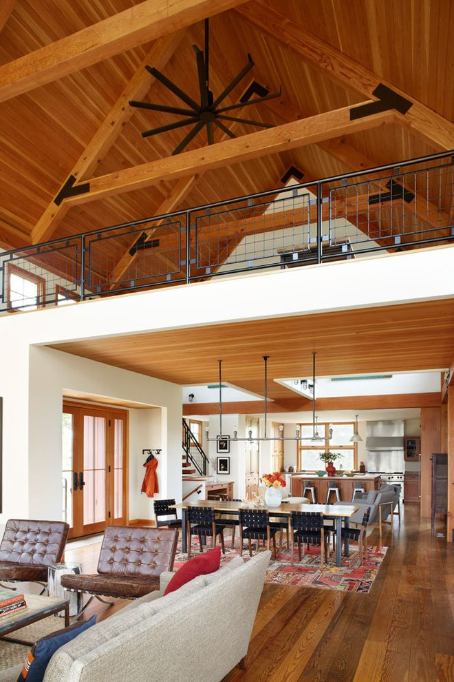 Amigo Power Equipment with Farmhouse Living Room  and Exposed Beams Farm House Leather Lounge Chairs Loft Metal Railing Modern Barn Open Floor Plan Pendant Lighting Roof Trusses Sloped Ceilings Sustainable Tall Ceilings Wood Ceiling Wood Flooring