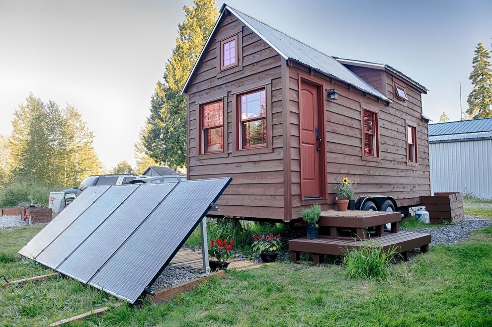 Amigo Power Equipment with Rustic Exterior Also Awning Window Gable Roof Grass Gravel Metal Roof Mobile Home Porch Light Potted Plants Red Door Red Flowers Red Siding Rustic Wood Siding Shed Dormer Solar Panels Sunflower Wall Lantern Wheels Wood Steps