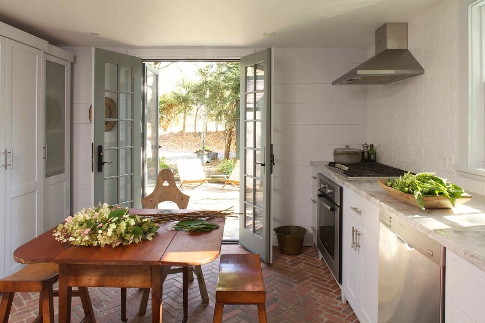 Anderson French Door Screen with Farmhouse Kitchen  and Brick Floor Eat in Kitchen Farmhouse Kitchen French Door French Doors Kitchen Table Marble Counter Wood Paneling Wood Table