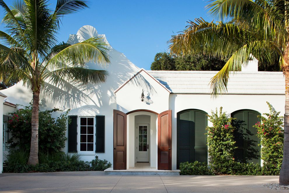 Argent Heating and Cooling with Tropical Exterior  and Arched Front Door Bushes Entryway Green Shutters Outdoor Lighting Palm Tree Red Flowers Shrubs Unique Exterior White Exterior White Roof White Siding Wood Front Door