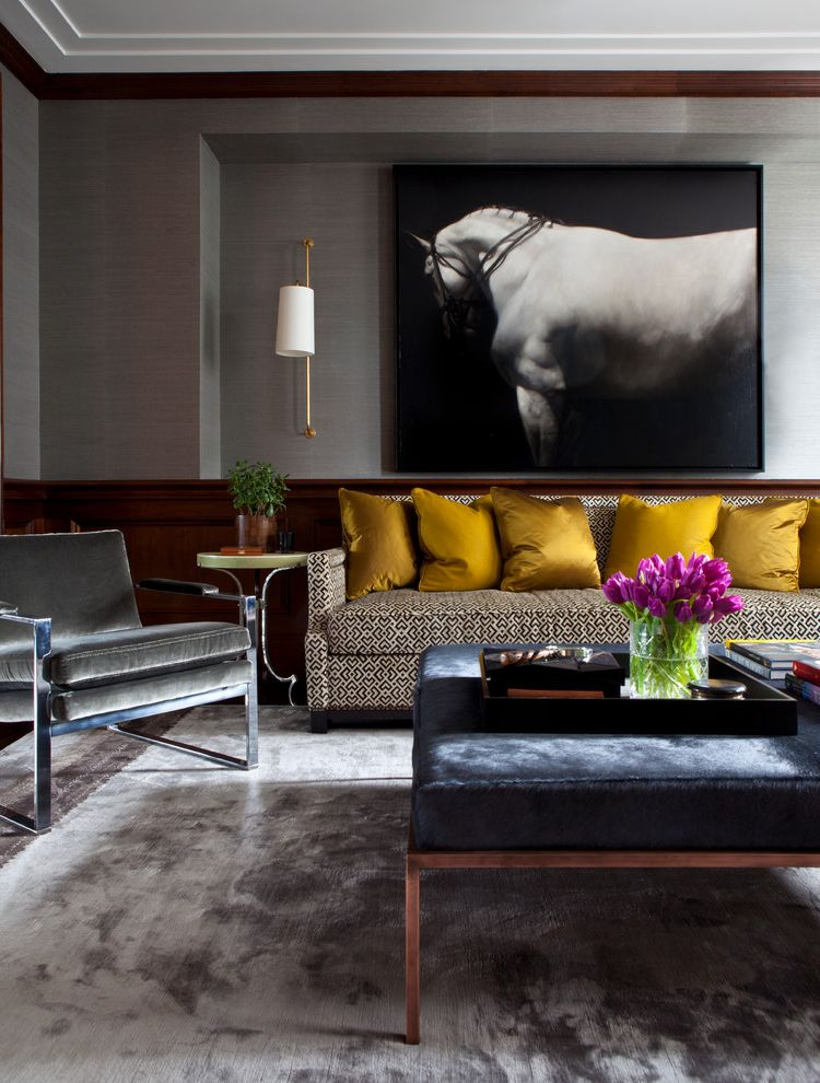 Art Van 14 Mile   Transitional Living Room  and Cowhide Bench Cowhide Coffee Table Dark Wood Trim Gold Pillows Grasscloth Gray Armchair Gray Rug Horse Art Horse Painting Masculine Pole Sconce Silk Rug White Ceiling Wood Wainscoting
