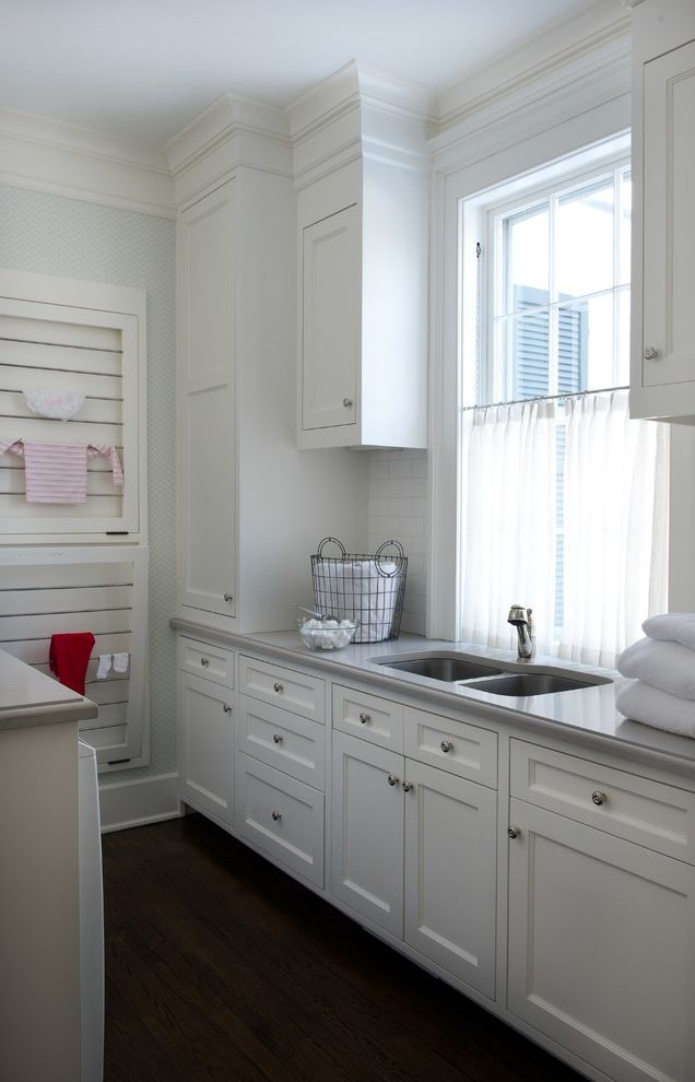 B Dry Basement with Traditional Laundry Room  and Built in Drying Rack Dark Wood Floor Drying Rack Laundry Basket Natural Lighting Utility Sink Wall Mounted Drying Rack White Cabinets White Drawers White Molding White Trim