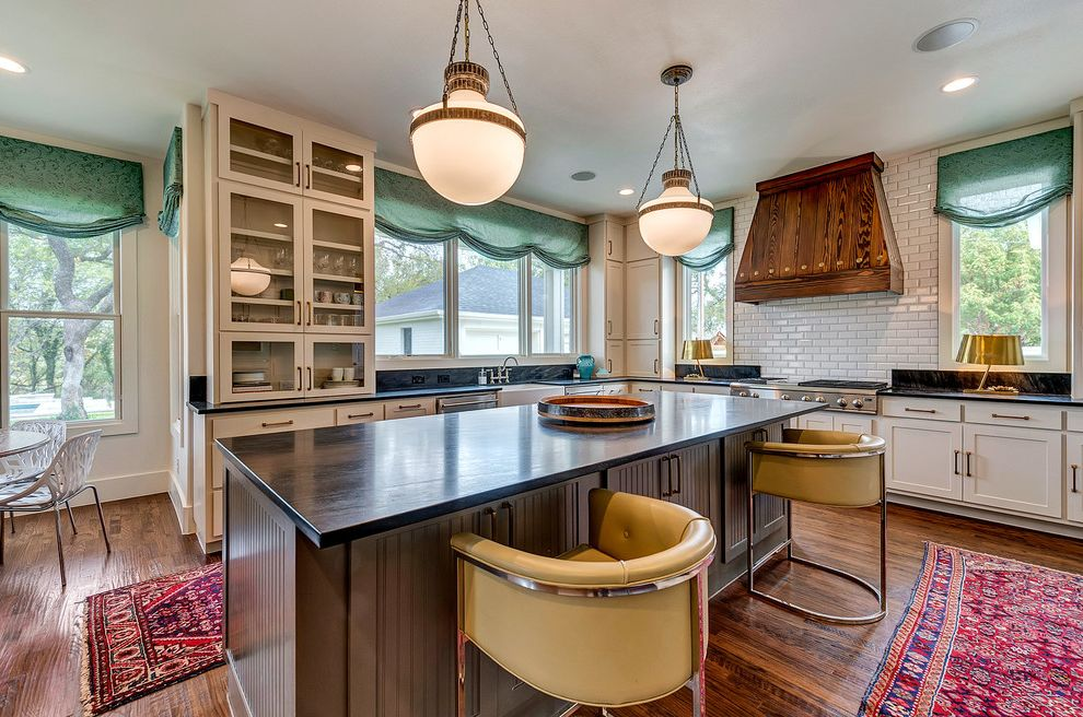 Bannister Custom Homes with Transitional Kitchen  and Beveled Subway Tiles Black Countertop Glass Front Cabinets Pendant Light Red Area Rug Soapstone Countertops Wood Range Hood