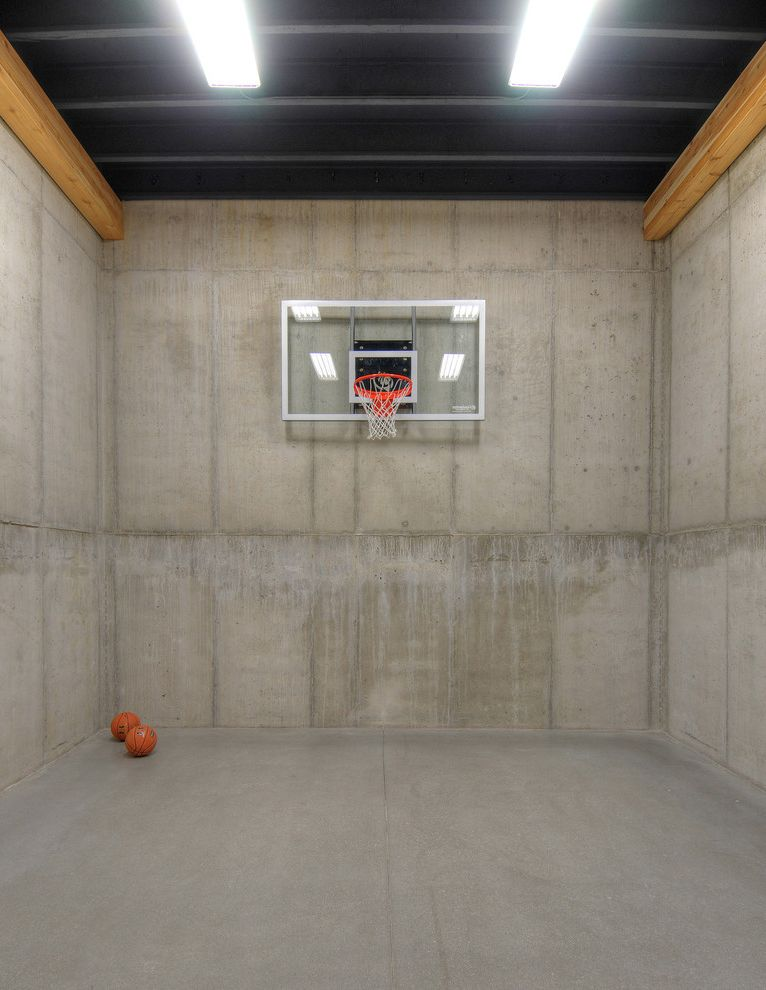 Basement in Spanish   Industrial Home Gym  and Basketball Court Concrete Walls Fluorescent Lighting Glass Backboard High Ceiling Wood Beams