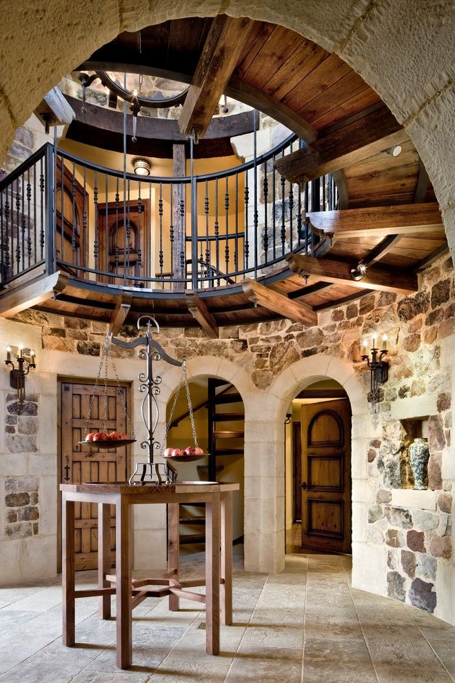 Basement in Spanish with Rustic Hall Also Arched Doorway Chandelier Iron Fence Rustic Rustic Chandelier Stone Floor Stone Wall Timber Walkway Wood Beams Wood Door Wood Table