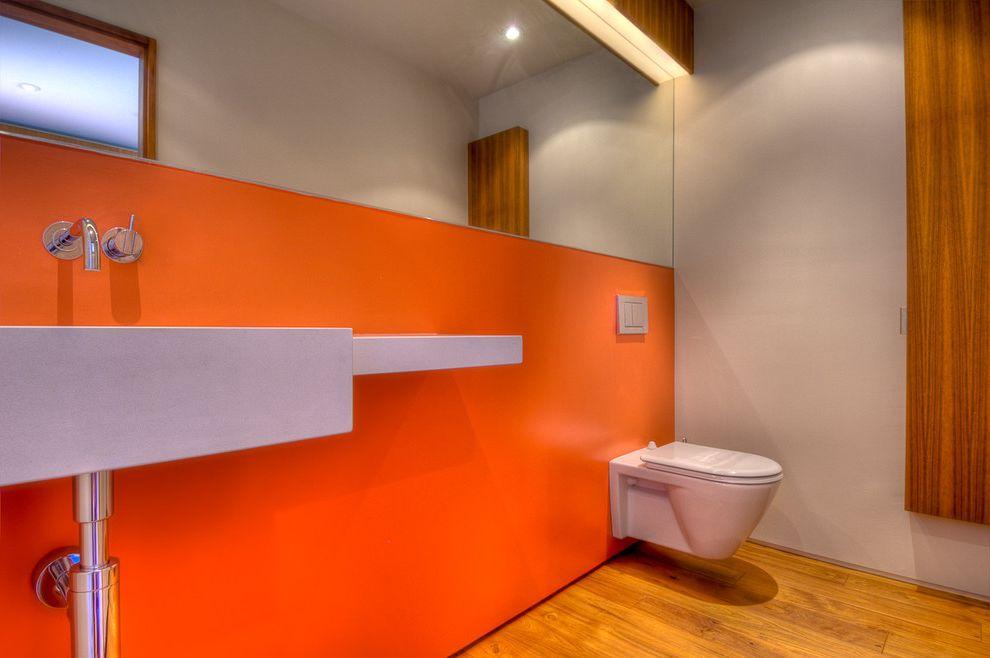 Basement Toilet   Modern Bathroom  and Accent Wall Bathroom Mirror Floating Toilet Minimal Orange Wall Wall Mount Faucet Wall Mount Sink Wall Mount Toilet Wood Flooring
