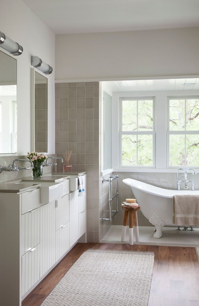 Bathtub Faucet with Sprayer with Farmhouse Bathroom  and Apron Sinks Bath Mat Bathroom Bathtub Beadboard Clawfoot Tub Double Hung Windows Flat Panel Cabinets Freestanding Bathtub Gray Tiles Mirrors Slipper Bathtub Tile Wall Sconces Wood Floor