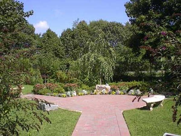 Bayport Flower House with Traditional Landscape  and Brick Pavers Concrete Bench Courtyard Courtyard Landscaping Custom Landscaping Outdoor Living