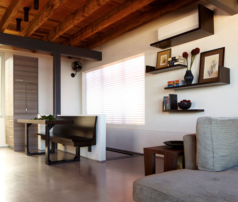 Bedroom Ac Unit   Modern Living Room  and Banquette Bench Seat Concrete Floor Corner Cabinet Dark Stained Wood Exposed Beams Floating Shelves Flush Cabinets Gray Seating Area Sheer Blinds Side Table Wall Fan White Walls