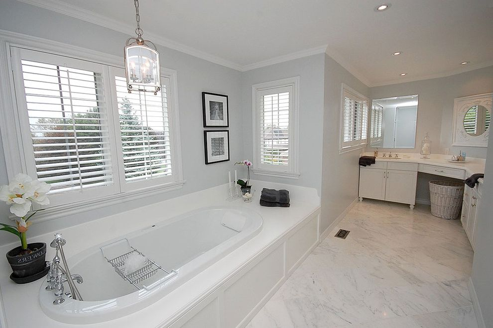 Benjamin Moore Decorators White with Traditional Bathroom  and Bathtub Black and White Photography Corner Vanity Laundry Basket Lighting Fixture Marble Floor Marble Tiles Pendant Light Plantation Shutters Soaker Tub Wood Blinds