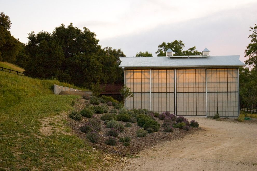Bennett Heating and Air with Farmhouse Shed  and Cupola Grass Hill Metal Roof Modern Barn Natural Light Shrubs Translucent Glass Panels Trees