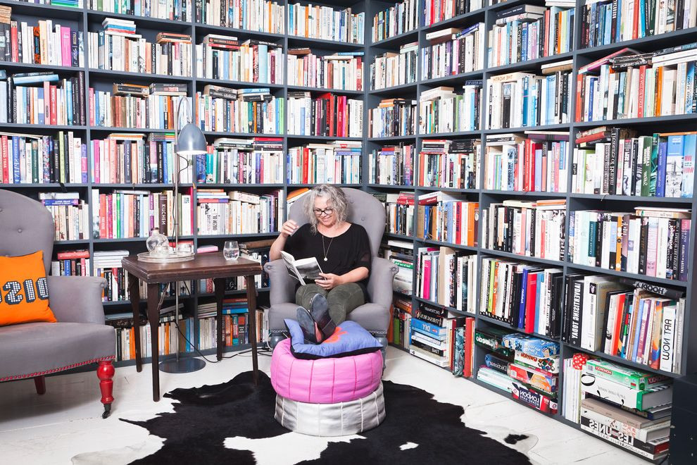 Bennett Property Management   Eclectic Home Office  and Animal Skin Rug Bookcase Books Cowhide Rug Library Library Room Library Wall Orange Pillow Pink Pouf Reading Room Silver Pouf