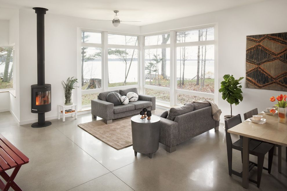 Best Flooring for Concrete Slab   Contemporary Family Room Also Area Rug Ceiling Fan Concrete Floor Corner Fireplace Great Room Grey Sofa House Plants Minimal Neutral Colors Open Floor Plan Symmetry Wood Burning Stove