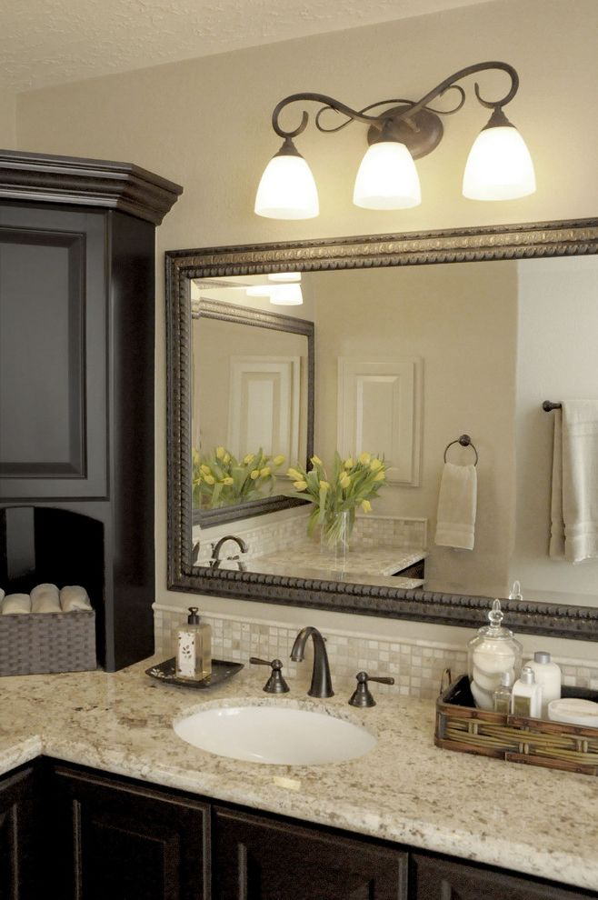 Black Vanity Light Fixtures with Traditional Bathroom  and Bath Accessories Bathroom Mirror Dark Wood Cabinets Fireplace Granite Countertops Neutral Colors Sconce Wall Lighting