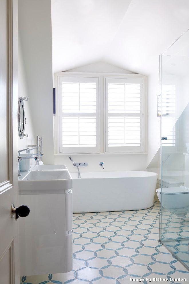 Blue Ceramic Floor Tile with Transitional Bathroom and Bathroom Floor Tile Bathroom Shutters Bathroom Tile Blue Blue and White Floor Tile Freestanding Bath Plantation Shutters Pop of Color Subtle Vaulted Ceiling White Bathroom
