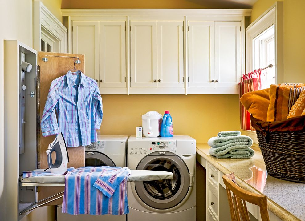 Boarding School Rooms with Traditional Laundry Room Also Built in Storage Fold Out Ironing Board Front Loading Washer and Dryer Gold Walls Ironing Boards Shaker Style Wall Ironing Board White Cabinets Wicker Basket Wood Cabinets