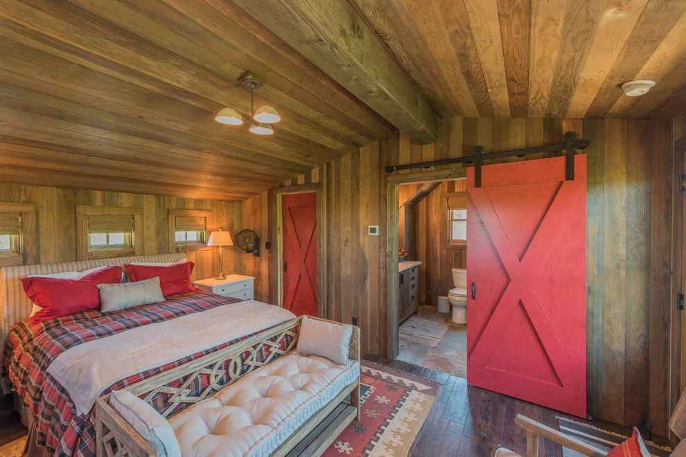 Boot Ranch Golf with Rustic Bedroom  and 3 Light Ceiling Pendant Cozy Cabin End of Bed Bench Exposed Beams Low Vaulted Ceiling Natural Fiber Shades Red Plaid Bedding Striped Upholstered Headboard Tufted Bench Cushion Warm Wood Walls and Ceiling