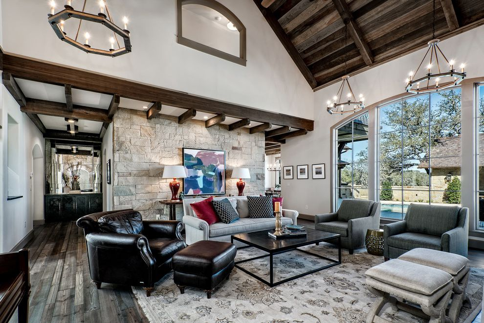 Boot Ranch Golf with Rustic Living Room Also Black Coffee Table Cathedral Ceilings Coffered Ceiling Dark Leather Arm Chair with Foot Stool Exposed Beams Gray Area Rug Gray Arm Chairs Gray Sofa Mini Chandelier Stone Accent Wall White Walls