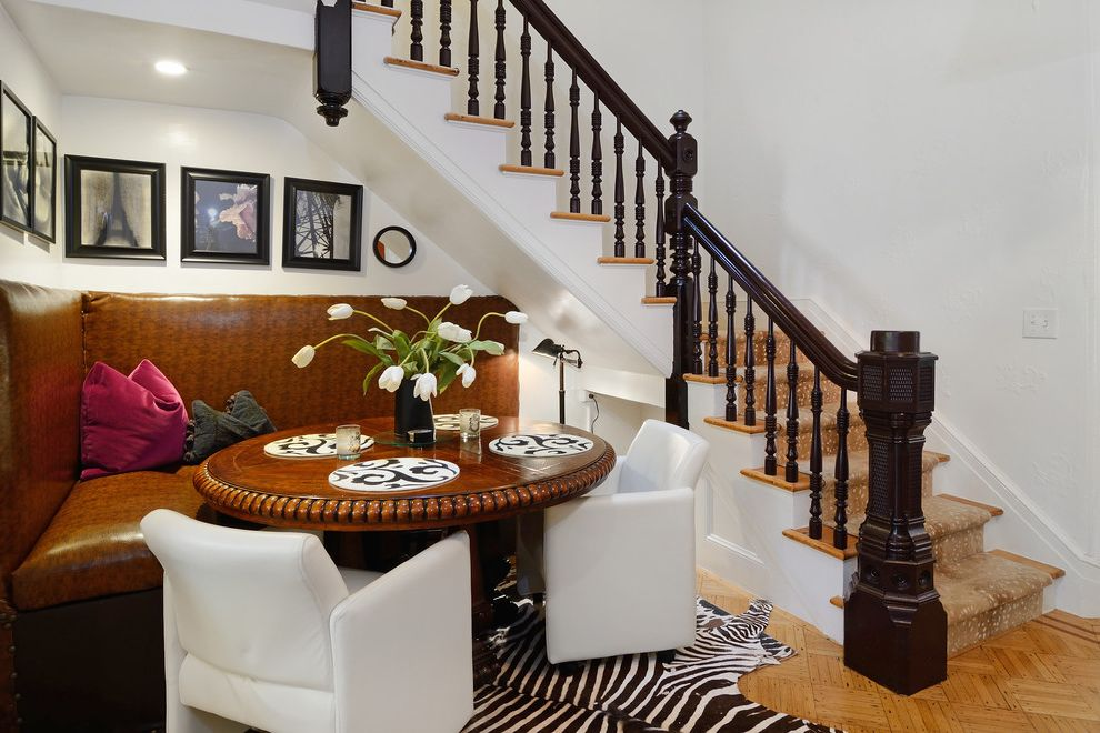 Brownstone Properties with Transitional Dining Room Also Dark Stained Wood Banister Leather Banquette Leather Dining Bench Light Wood Floor Newel Post Round Dining Table White Leather Dining Chairs White Walls Zebra Rug