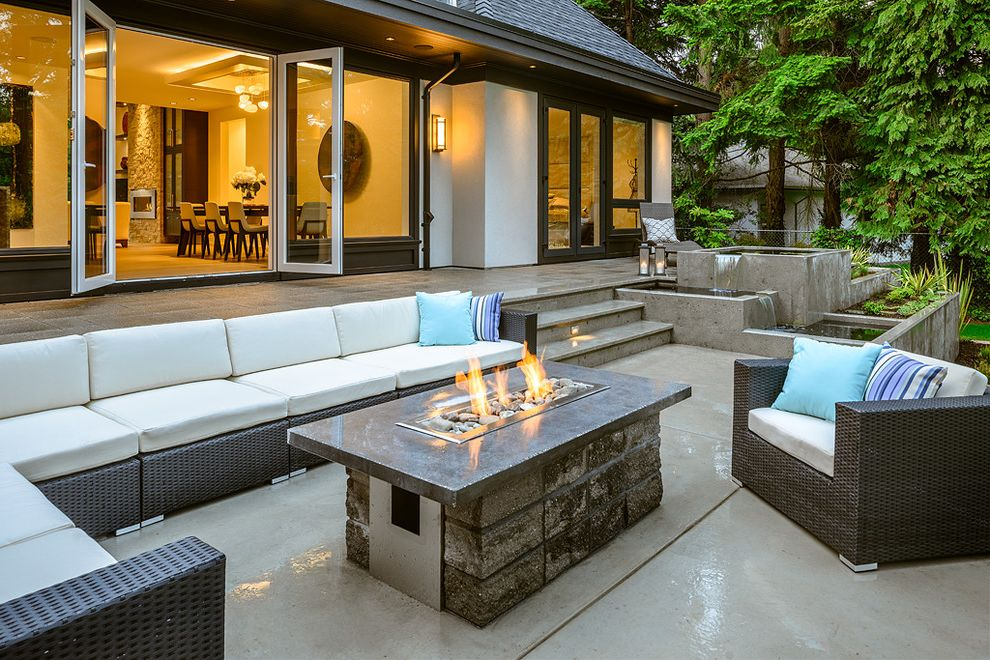 Build a Propane Fire Pit with Contemporary Patio and Blue Concrete Patio Fire and Water Features Firepit Large Windows Pillows Planter Boxes Seat Cushions Steps Stripes Wall Sconces Water Feature Waterfall White White Exterior Woven Outdoor Furniture