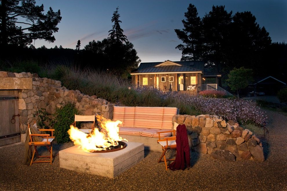 Build a Propane Fire Pit with Farmhouse Patio and Board Formed Concrete Built in Bench Campaign Chair Directors Chair Fire Pit Grasses Gravel Mass Planting Patio Furniture Stone Wall