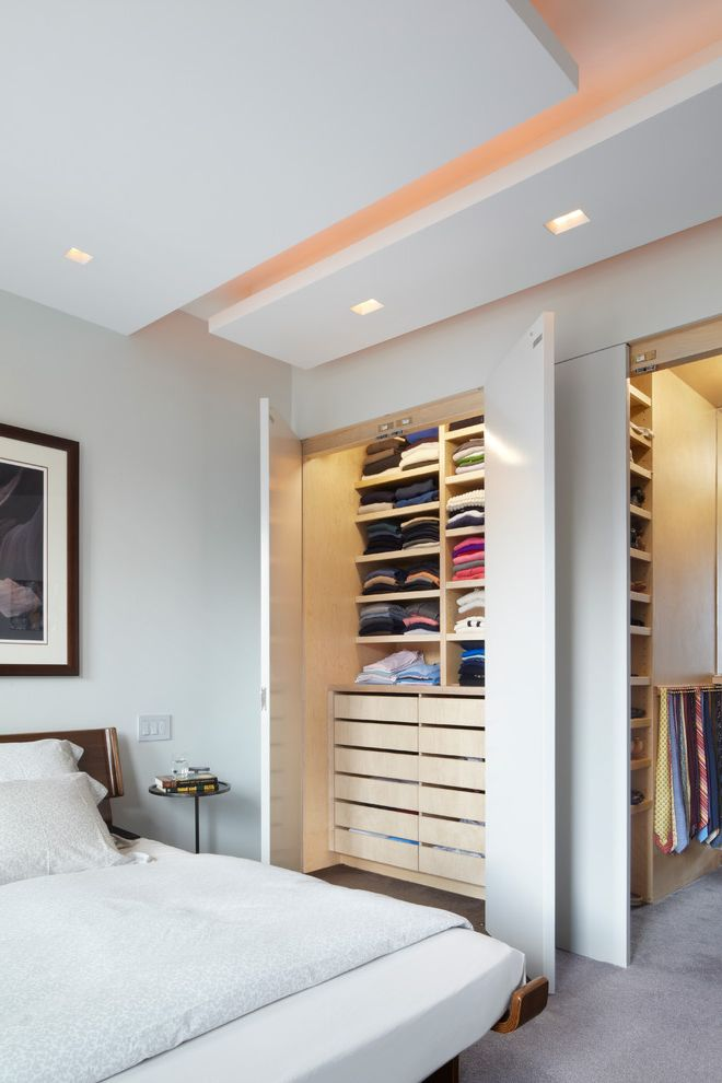 Building Shelves in Closet with Contemporary Bedroom  and Ceiling Platform Closet Doors Closet Drawers Closet Shelves Cove Lighting Light Wood Drawers Light Wood Shelves Open Shelves Open Shelving Recessed Lighting White Bedding White Wall