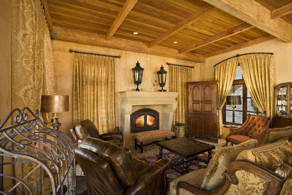 Burns Pest Elimination   Mediterranean Living Room  and Area Rug Carved Stone Fireplace Coffee Table Curtains Damask Drapes Floor Lamps Fringe Gold Lanterns Leather Armchair Ottoman Seating Area Tufted Upholstery Window Treatment Wood Beams Wood Ceiling