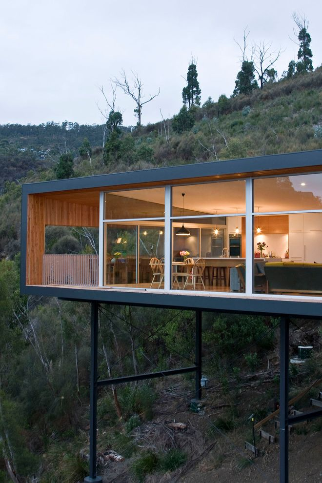 Buying Land to Build a House   Modern Exterior Also Elevated Glass Wall Hillside Pilons Timber Motif Timber Throughout