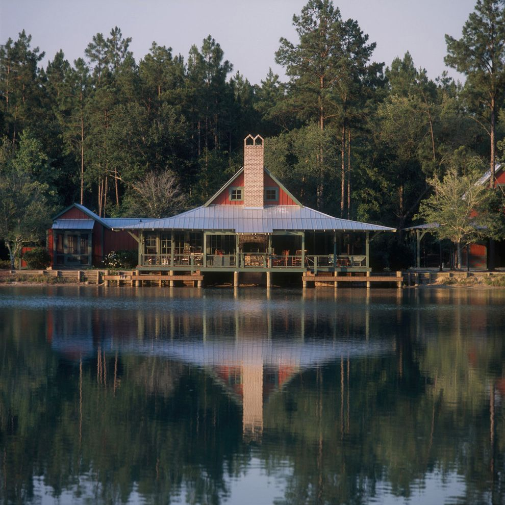 Camp Lejeune Housing with Rustic Exterior Also Board and Batten Siding Boathouse Brick Chimney Dock Green Trim Lake Lake View Metal Bead Roof Metal Roof Red Brick Chimney Red Siding Standing Seam Roof Vertical Metal Roof Wharf