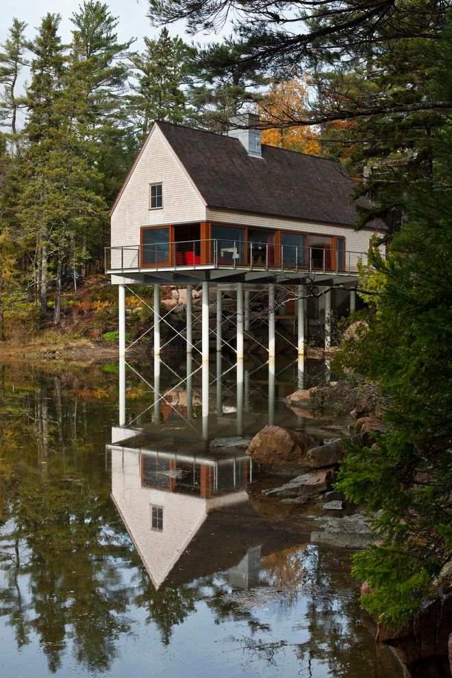Camp Lejeune Housing with Rustic Exterior  and a Frame Boulders Cable Railing Chimney Cottage Elevated House Maine New England Pond Pond House Posts Secluded Natural Landscape Waterfront Window Wall Wood Siding Wood Window Trim