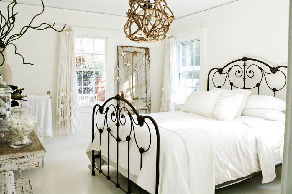 Cast Iron Headboard with Shabby Chic Style Bedroom Also Beach Cottage Curtain Panels Distressed Furniture Driftwood Guest Room Iron Bed Neutral Colors Pendant Light Salvaged Door Shabby Chic White Bedding White Painted Floor