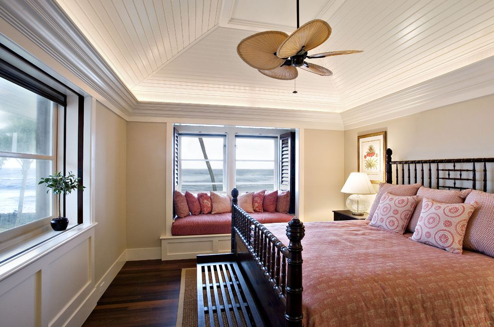 Ceiling Fan with Palm Leaf Blades with Tropical Bedroom  and Baseboard Beige Wall Black Bed Ceiling Fan Foot of the Bed Pink Duvet Sloped Ceiling Vaulted Ceiling View White Wood Window Seat Window Shutters Wood Ceiling Wood Flooring Wood Trim