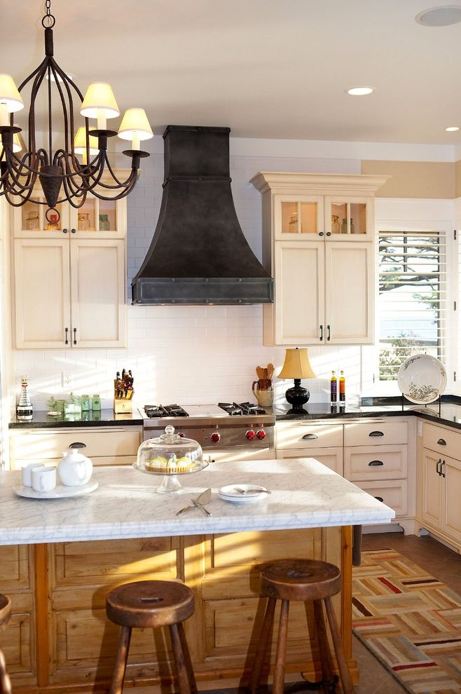 Ceiling Mount Vent Hood with Traditional Kitchen Also Black Countertop Black Range Hood Chandelier Cooktop Glass Cabinets Kitchen Island White Cabinets White Countertop White Subway Tile White Tile Backsplash Wood Barstools Wood Kitchen Island