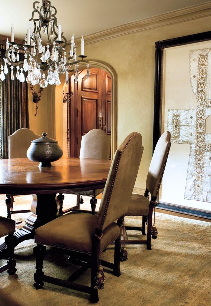 Chandelier Definition with Mediterranean Dining Room Also Arched Doorways Area Rug Chandelier Crown Molding Faux Finish Nailhead Trim Neutral Colors Oversized Pedestal Table Round Dining Table Upholstered Dining Chairs Wall Art Wall Decor