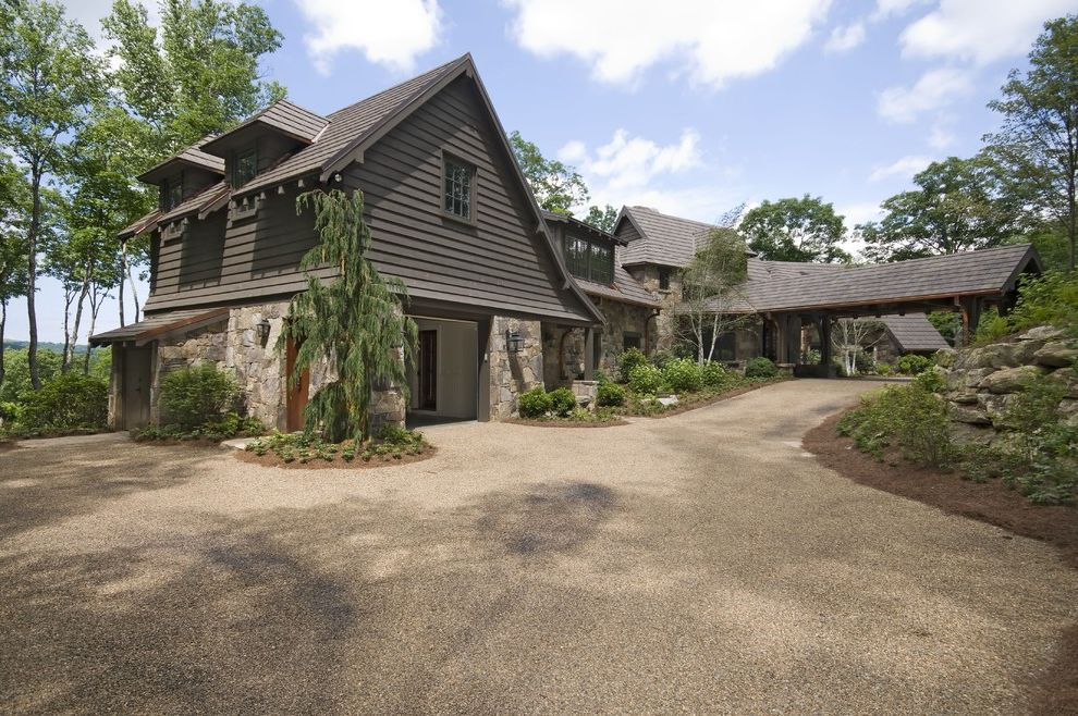 Chip Seal Driveway with Rustic Exterior and Boulder Cabin Carport Dormer Windows Eaves Entrance Entry Gravel Driveway Lantern Outdoor Lighting Overhang Retaining Wall Rock Wall Rustic Wall Lighting Wood Siding