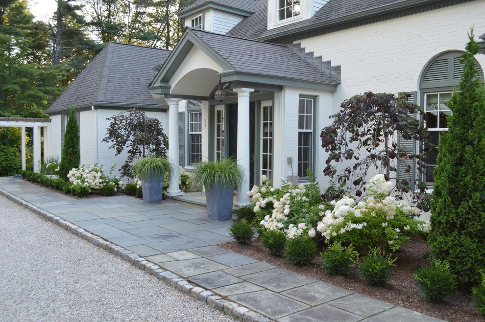 Chip Seal Driveway with Traditional Landscape and Arched Window Bluestone Paving Chip and Seal Driveway Formal Courtyard Granite Cobble Edging Potted Plants Shingle Roof White Brick Exterior White Columns