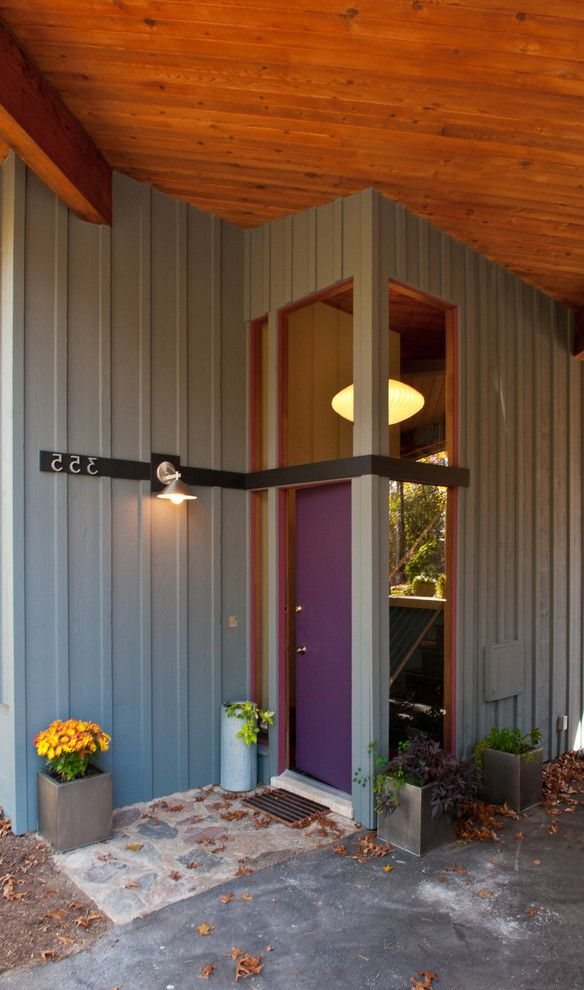 Coast to Coast Movers with Modern Entry Also Board and Batten Container Plants Covered Entry Entry House Numbers Outdoor Lighting Potted Plants Purple Front Door Roof Overhang Transom Wood Ceiling Wood Siding