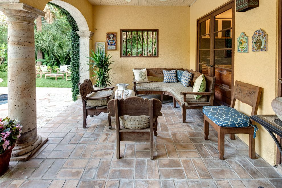 Collis Roofing   Mediterranean Patio  and Brick Carved Wood Columns Covered Patio Eclectic Patio Limestone Pavers Pillows Pool Patio Potted Plants Seat Cushions Stucco Tile Wall Art Transitional Patio Yellow