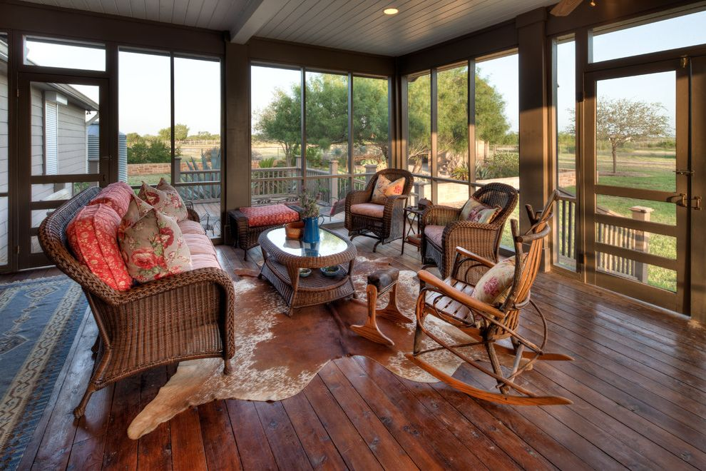 Collis Roofing   Traditional Porch  and Animal Hide Rug Country Interiors Cozy Porch Deck Floor Rustic Furniture Rustic Interiors Screen Porch Screened in Porch Wicker Chairs Wicker Coffee Table Wicker Sofa Wood Floor Wood Rocking Chair