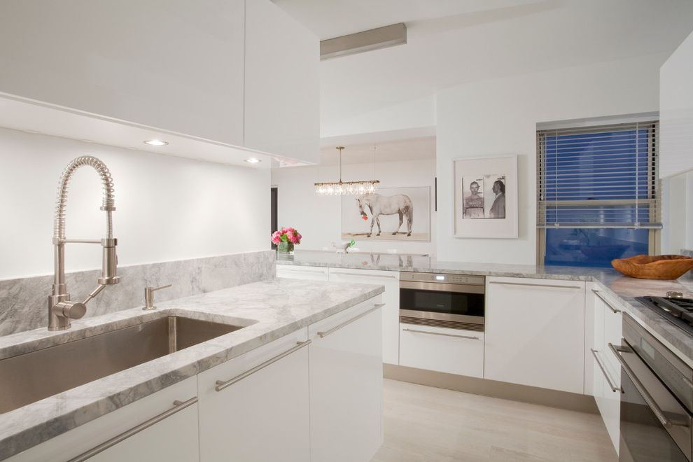 Colonial White Granite Countertops with Scandinavian Kitchen  and Artwork Linear Chandelier Porcelanosa White Kitchen Cabinets Stainless Steel Appliances Undercabinet Lighting White Kitchen