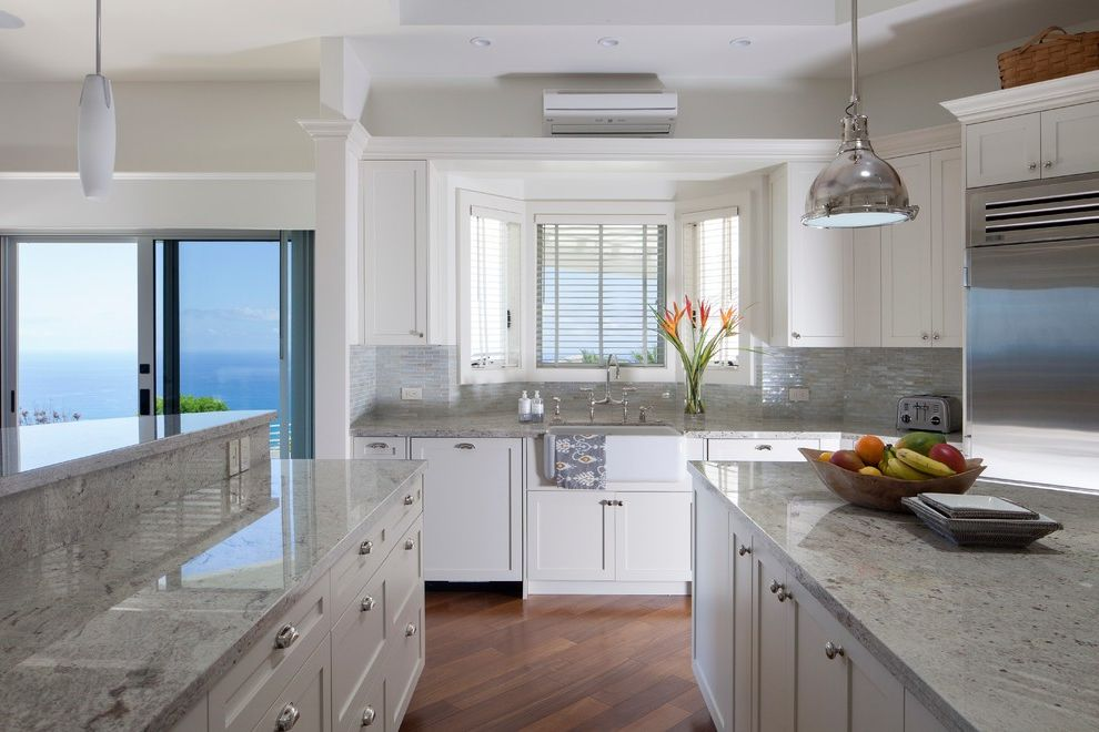 Colonial White Granite Countertops with Tropical Kitchen  and Airy Blinds Double White Island Farmhouse Sink Neutral Colors Pendant Lights Recessed Lights Sliding Glass Doors Small Tile Backsplash Stainless Steel Appliances White Cabinets Window