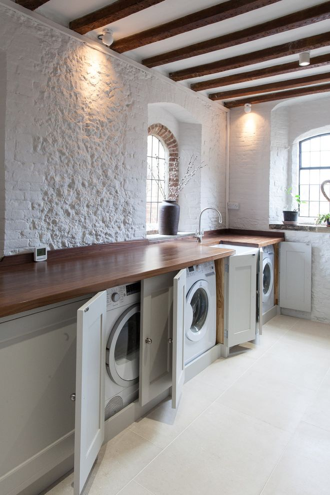 Commercial Grade Washing Machine   Farmhouse Laundry Room Also Built in Cabinet Country Country Utiity Covered Washer Dryer Exposed Brick Wall Exposed Wood Beams Painted Brick Pastel Green Cabinet White Brick Wall Wooden Worktop