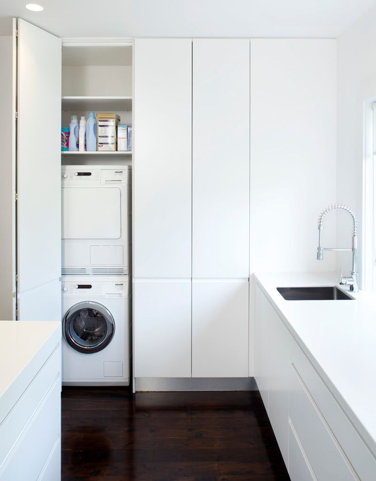 Commercial Grade Washing Machine   Modern Laundry Room  and Flat Panel Cabinets Hidden Laundry Appliances Single Bowl Sink Stackable Washer and Dryer Stacked Washer and Dryer White Cabinets White Counters Wood Floors