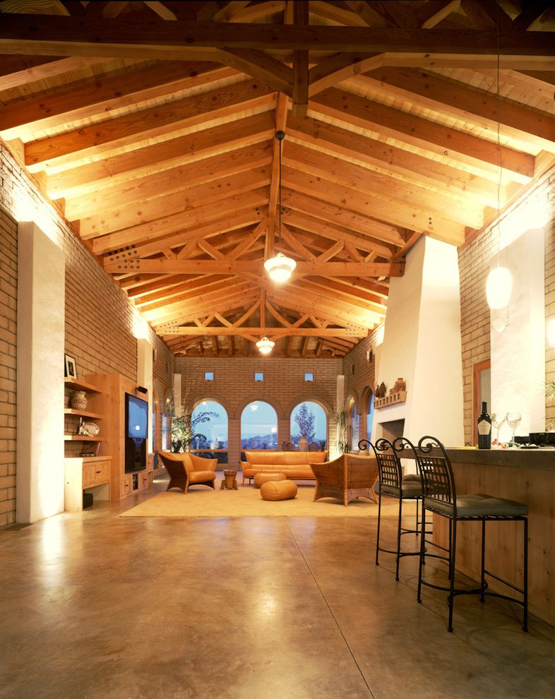 Concrete Staining Oc with Rustic Living Room Also Area Rug Breakfast Bar Brick Walls Concrete Flooring Exposed Beams Great Room Neutral Colors Open Floor Plan Pendant Lighting Rustic Vaulted Ceiling Wood Ceiling
