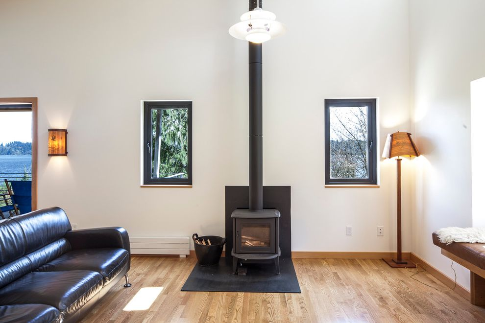 Conduction Stove   Modern Living Room  and Black Sofa Black Window Trim Cabin Floor Lamp Glass Doors Hardwood Floors Leather Sofa Modern Rustic Sconce Window Seat Wood Stove Wood Trim Woods Woodsy